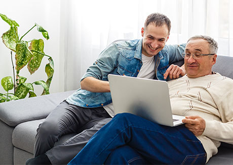 Father and son on computer researching untreated hearing loss