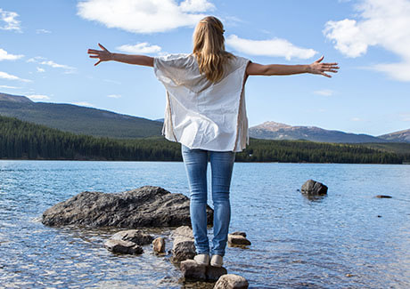 Woman balancing on rock staring at a lake thinking about hearing healthcare
