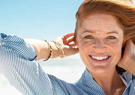 Woman living with tinnitus smiling on the beach