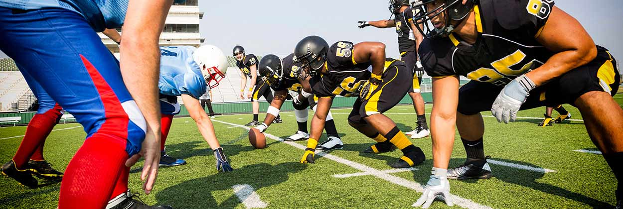 High school football players, line of scrimmage ready to tackle potentially causing hearing damage