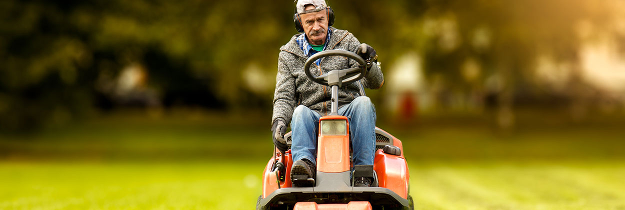 Man mowing lawn with hearing protection
